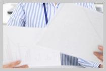 業務用シュレッダーを細断しちゃダメなものを注意する女性