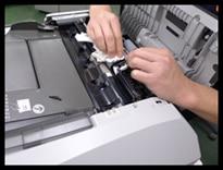 中古コピー機の給紙ローラーのクリーニングをしている様子