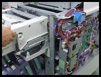 中古印刷機を分解し、内部の状況を確認している様子
