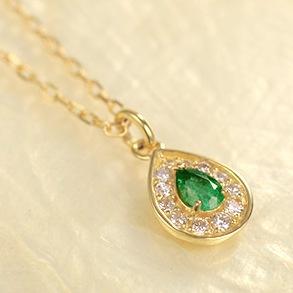 メインストーンのエメラルドをメレダイヤで取り巻いたK18ネックレスの画像