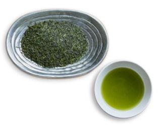 深い蒸し茶の茶葉と水色のイメージ写真