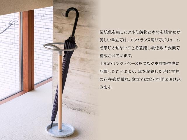 伝統色を施したアルミ鋳物と木材を組合せが美しい傘立ては、エントランス周りでボリュームを感じさせないことを意識し最低限の要素で構成されています。上部のリングとベースをつなぐ支柱を中央に配置したことにより、傘を収納した時に支柱の存在感が薄れ、傘立ては傘と空間に溶け込みます。