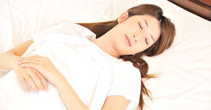 両腕を組んで眠る女性