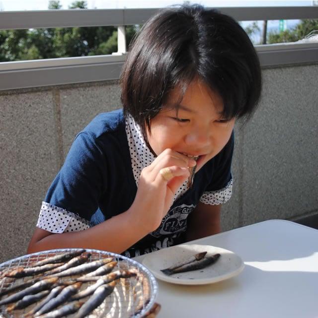 子供がウルメいわし丸干を食べている写真