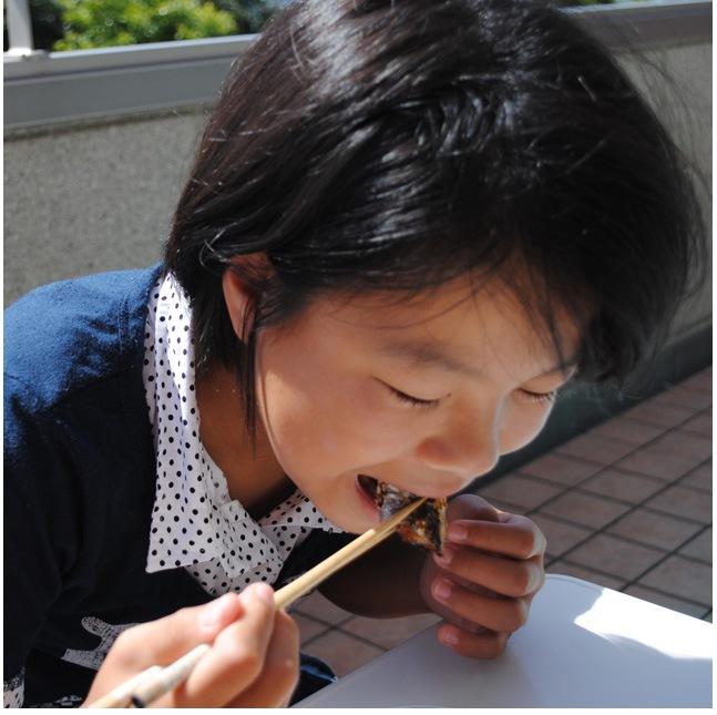 秋刀魚干物を子供が食べている写真