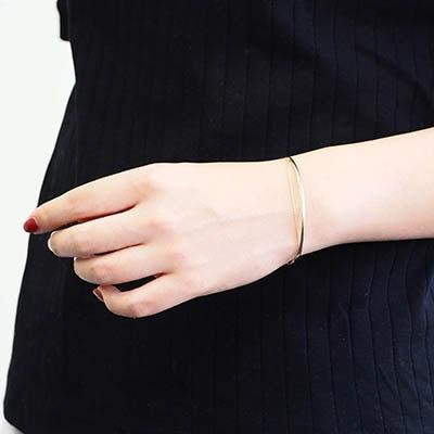 チェーンが施されたゴールドバングル。手首周りをスッキリ、品良く仕上げます。