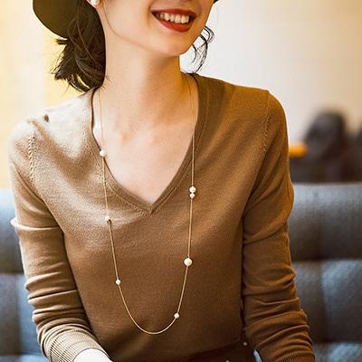 胸元を彩るコットンパールのネックレス。パーティシーンなど華やかな席には程よくボリュームを感じる上品なセレクトを。