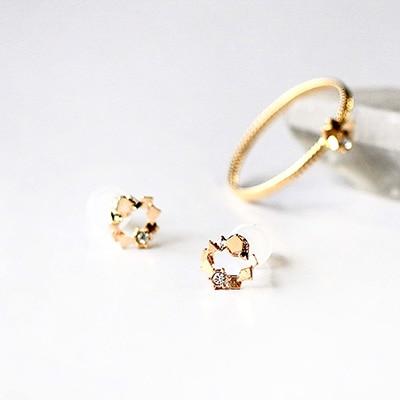 華奢なゴールドパーツが小さなサークルを描いたセラミックポストピアス。スワロフスキーがワンポイントに。