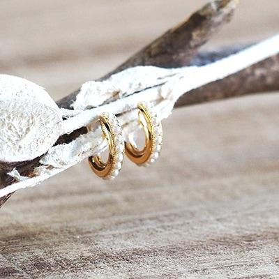 ゴールドのフレームにパールをあしらった、耳に沿うタイプのフープデザイン。程よいボリュームで、甘さと上品さのバランスがよく、優しい雰囲気をつくる優秀アイテム/