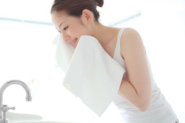 洗顔後タオルで顔を拭く女性