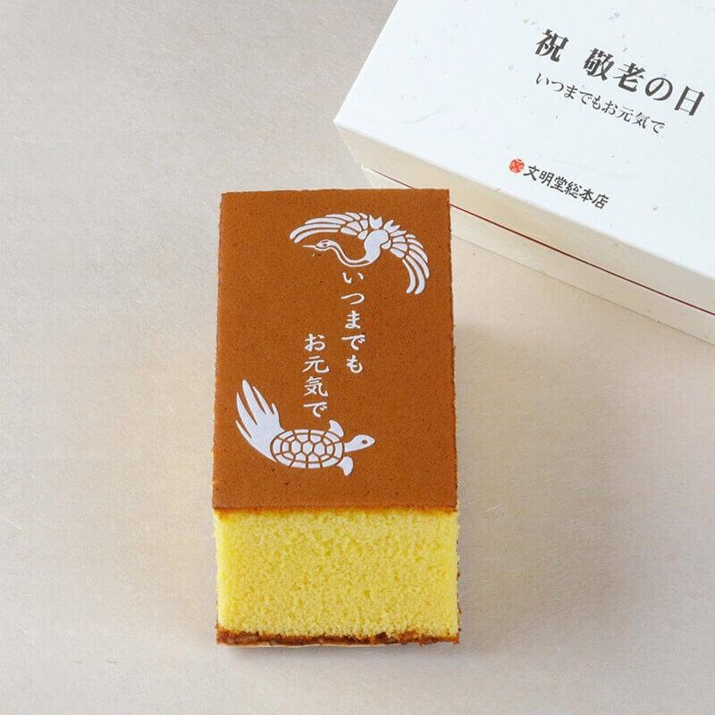 ホワイトチョコで鶴と亀のイラストとメッセージを刷り込んだ敬老の日カステラ