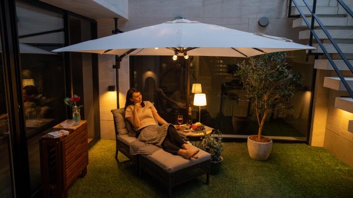 パラシェードスクエア,夜自宅の庭でくつろぐ女性の写真