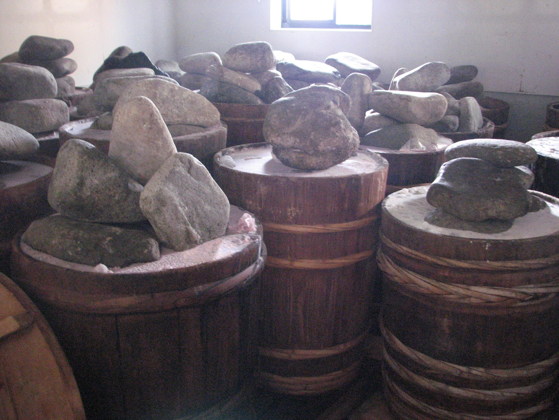 (重しの石が不規則に乗った木樽が沢山並んでる、やや白っぽい写真)