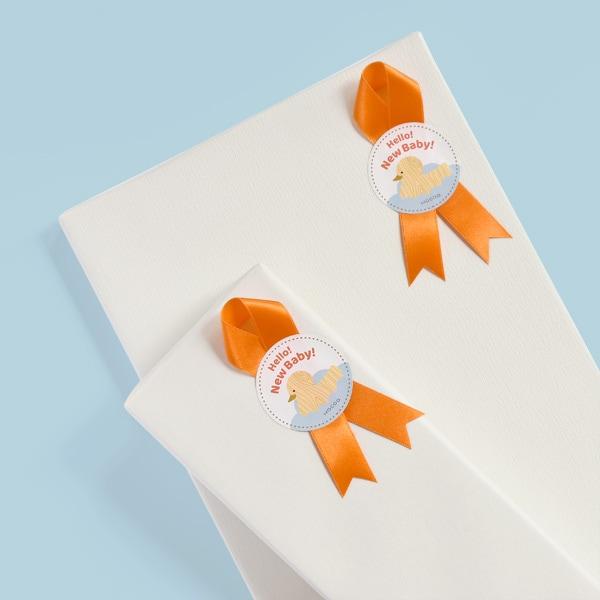 白和紙にオレンジのリボンシールのラッピング。