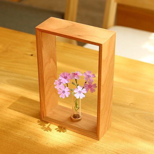 シンプルなデザインの無垢材フレームが、活けられた花をアート性高く美しく引き立てる一輪挿しです