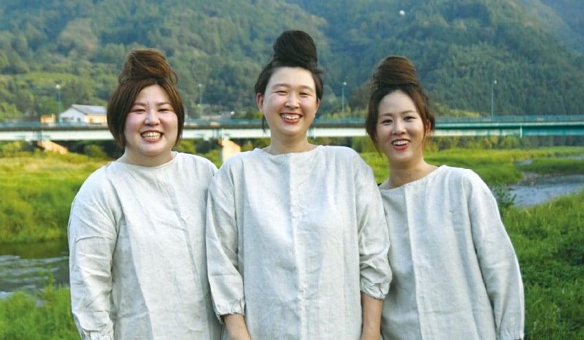 山なみを背景に女性3人が笑っている
