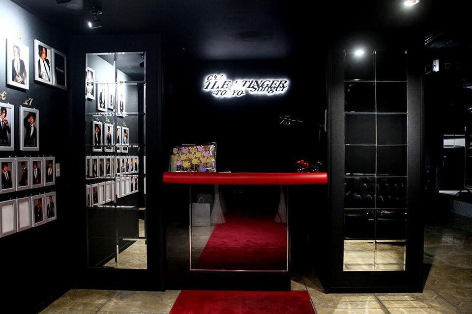 店の入り口とバックライトにより浮かび上がる店舗ロゴ