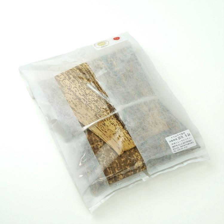 肉を竹の皮に包んで和紙調袋に入れる