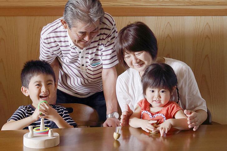 森のキノコのこまわなげで遊ぶおじいちゃん・おばあちゃんとお孫さんの画像