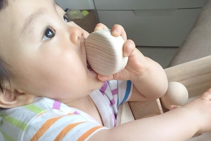 まぁるいかたちのはいったつみきを舐める赤ちゃんの画像