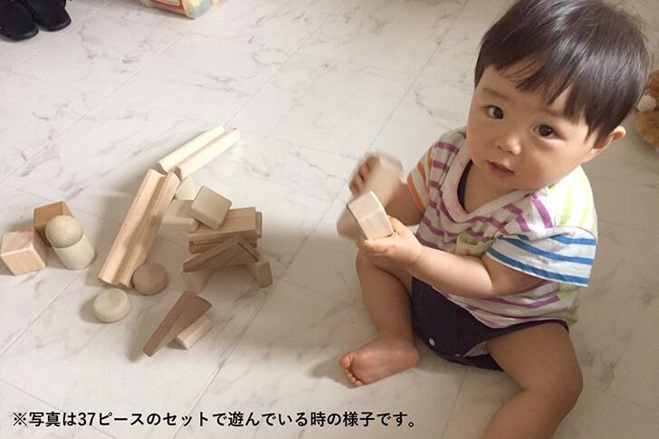 まぁるいかたちのはいったつみきで遊ぶ赤ちゃんの画像