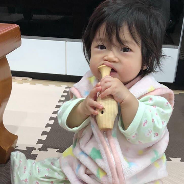 めんコイがらがらを舐める赤ちゃんの画像