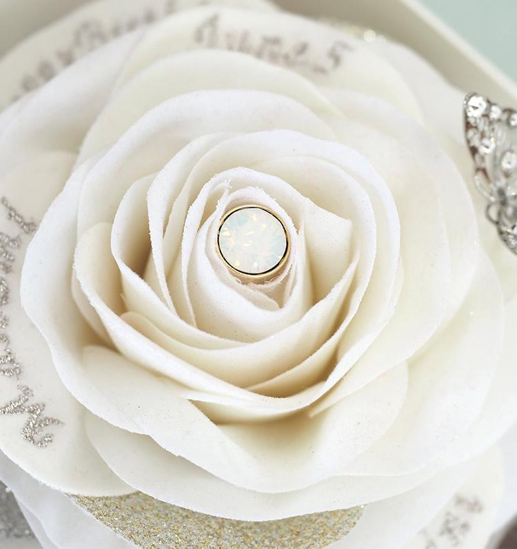 白いバラの中心に光る一粒の石