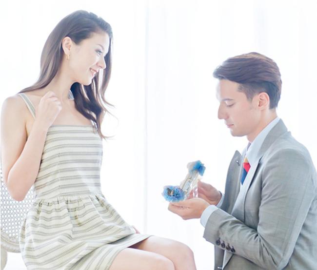 彼女の前でひざまずき、ガラスの靴を両手で差し出してプロポーズ