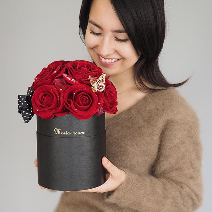 赤バラの花束を抱える女性