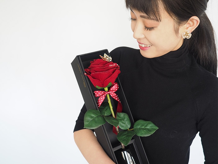 赤バラのプレゼントに喜ぶ女性