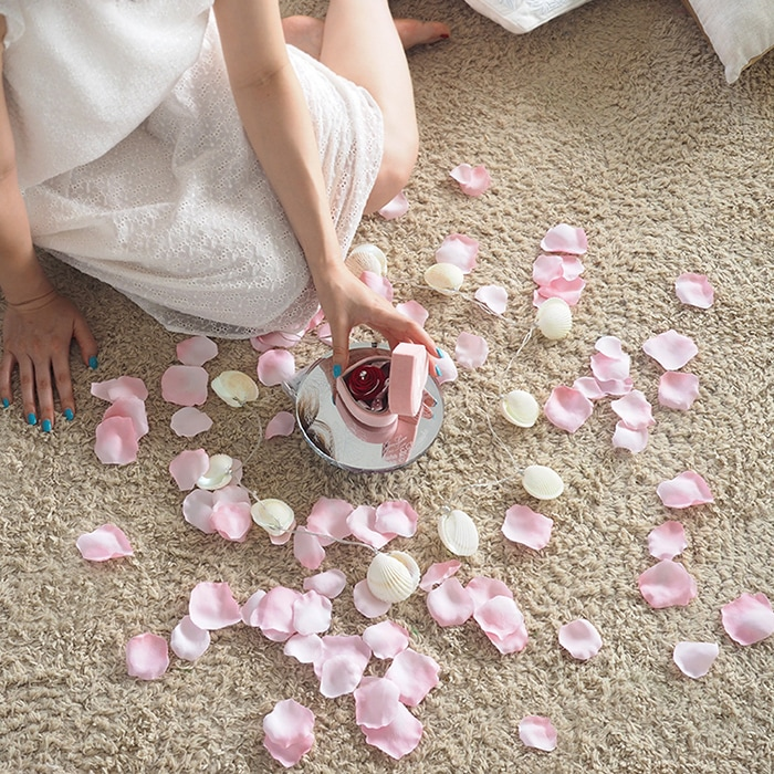 天然貝のLEDキャンドルライトと輝くクリスタルミラースタンド、そして淡いピンクのバラの花びら(造花)
