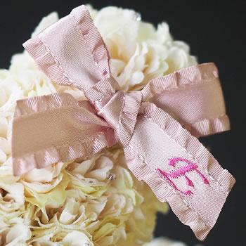 ピンクのリボンに刺繍する彼女のイニシャル