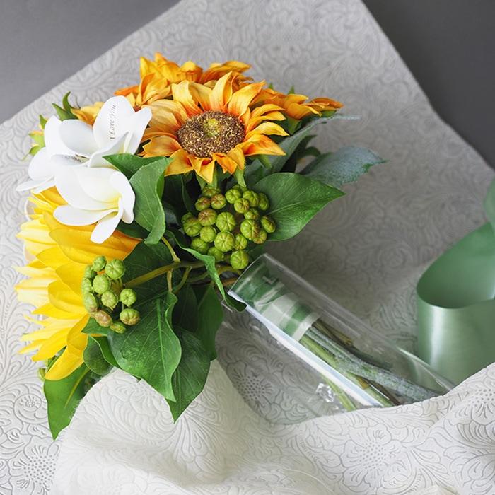 ひまわりの花束のラッピングをほどくと花瓶が登場!