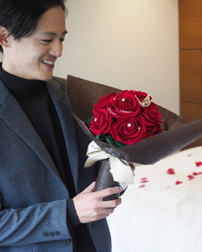 赤バラの花束を持つ男性