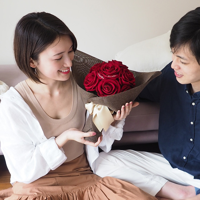 赤バラの花束のプレゼントに喜ぶ彼女