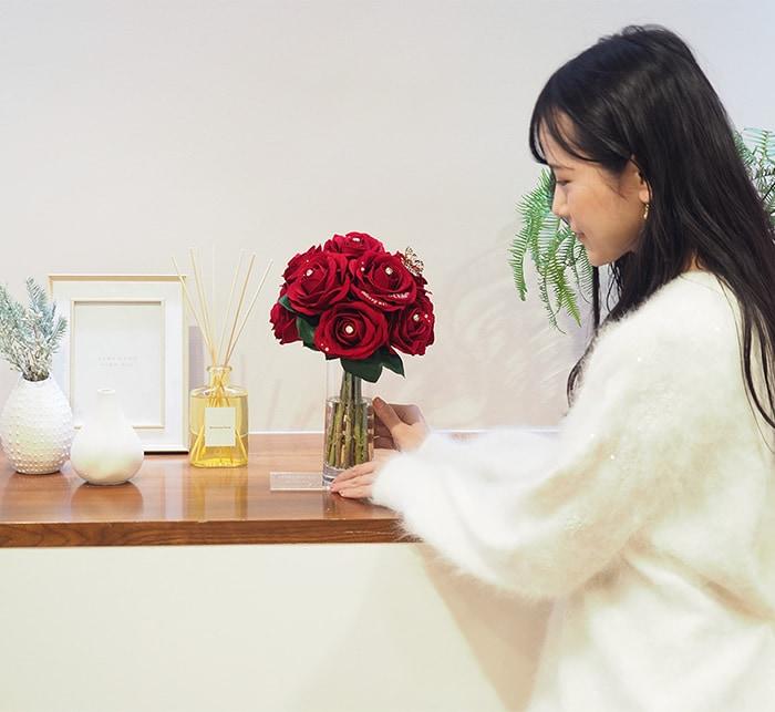 赤バラの花束を受け取る女性