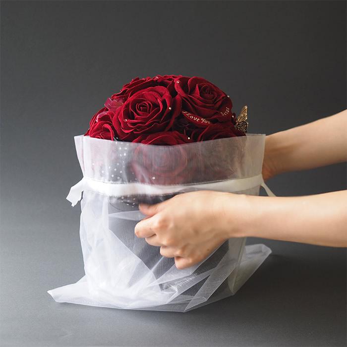 オーガンジーの袋から赤バラを取り出す