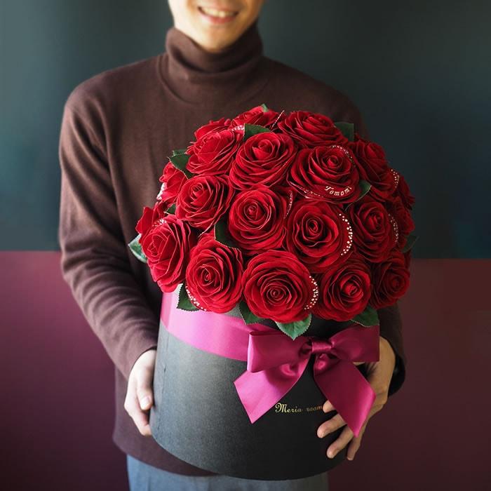 赤バラのボックスを持つ男性