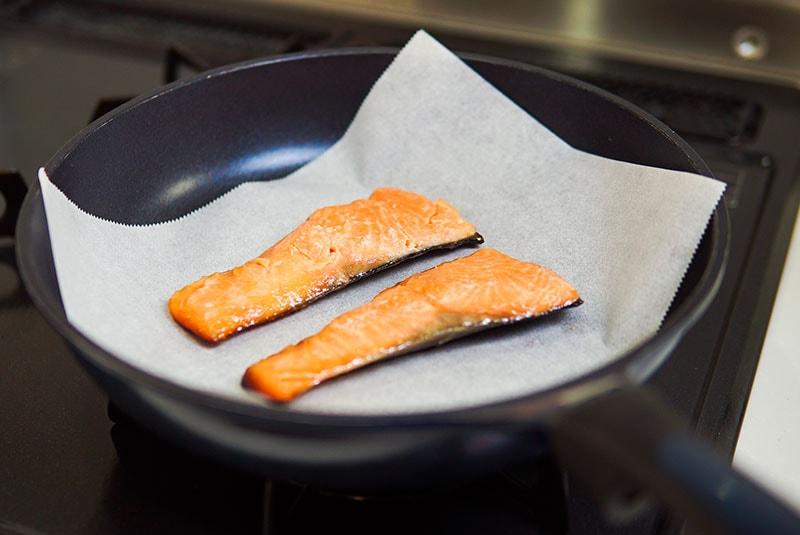 クッキングシートの上に魚を置いている様子の写真