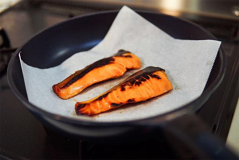 クッキングシートの上に焼き魚を置いている様子の写真