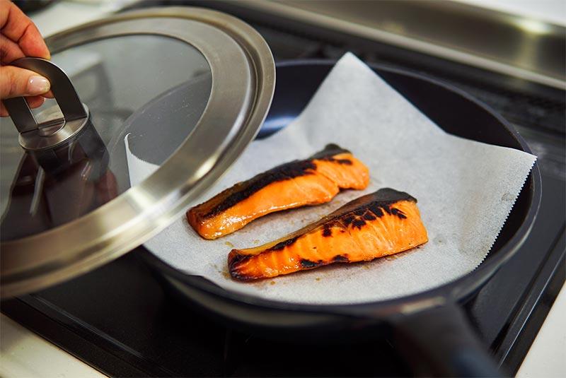 クッキングシートの上に焼き魚を置いてその上に蓋をしようとしている様子の写真