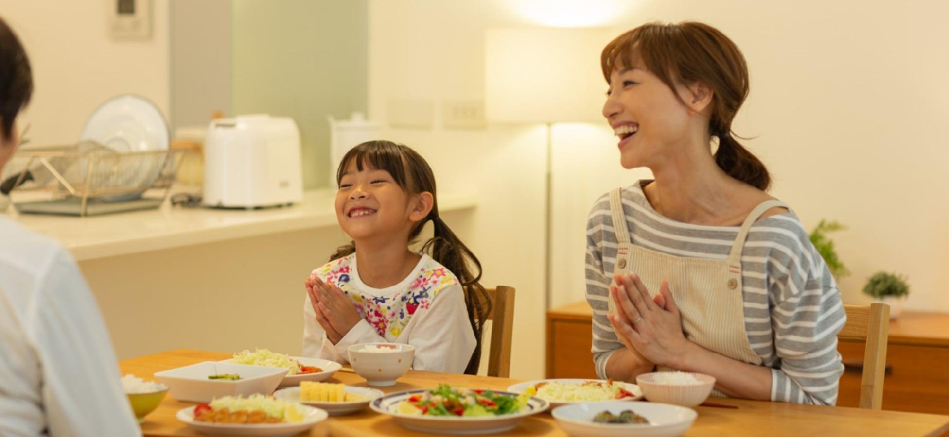 食卓でおいしいごはんをたのしむ家族の写真です。