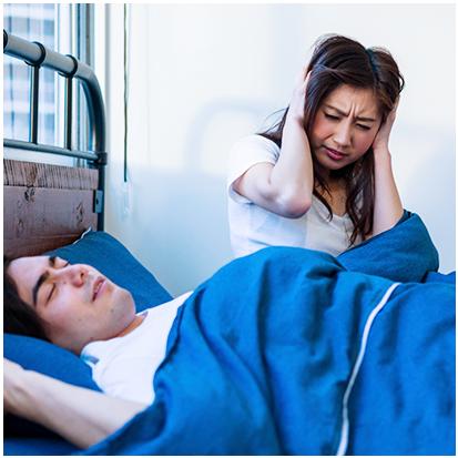 眠っている男性と耳を塞いでいる女性