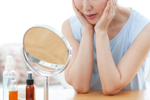 鏡を見て両手で顔を触る女性