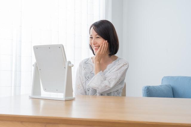 鏡に向かって微笑んでいる女性