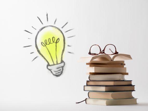 積み上げられた本と電球のイラスト