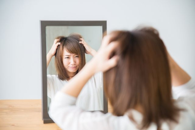 鏡で髪を確認する女性