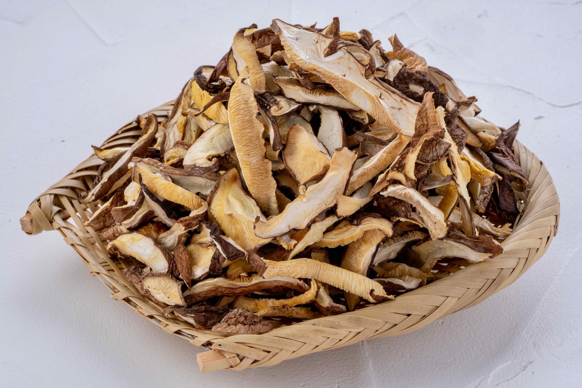 竹ざるに山盛りの原木栽培の乾燥椎茸スライス,北海道産のだし用乾燥シイタケ