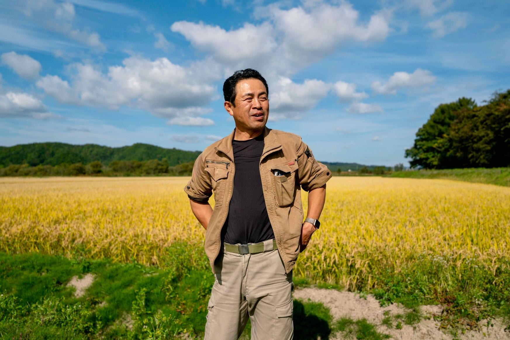 北海道むかわ町の小坂農園,黄金色の稲穂の前に立つ小坂さん