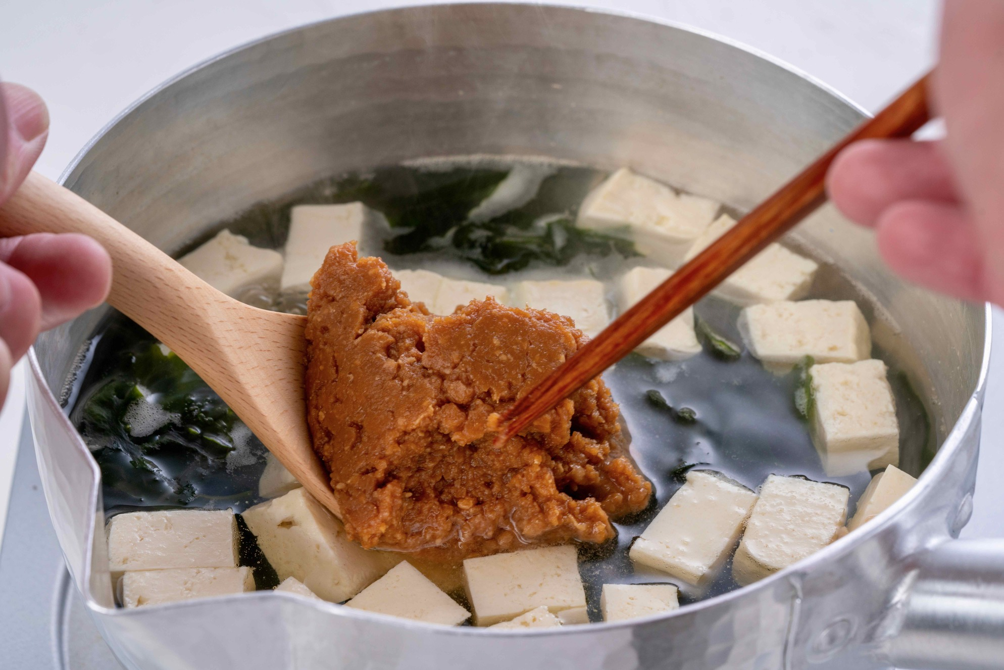 具とお湯が入った雪平鍋の中で味噌を溶く,豆腐とわかめの味噌汁